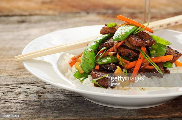 Stir fry meal including beef, peas, carrots, and rice