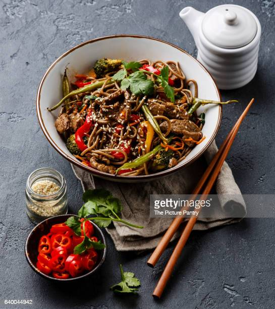 Stir fry noodles soba with beef and vegetables in bowl on dark stone background