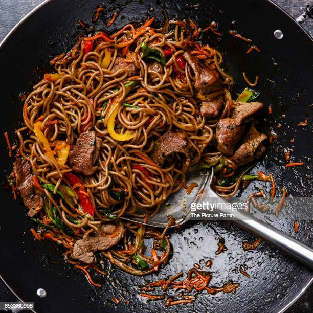 Stir fry soba noodles with beef and vegetables in wok pan close up