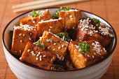 Stir fry tofu with sesame seeds and herbs in a bowl close-up. horizontal
