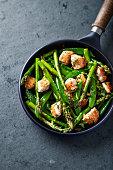 Stir-fried sesame chicken, green asparagus and sugar snap peas in a pan