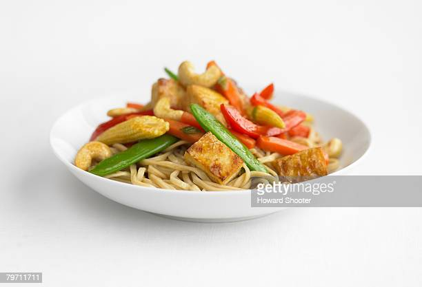 Stir-fry with noodles in a white dish, close up