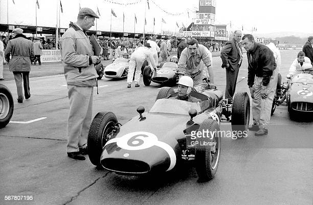 Stirling Moss in a Rob Walker Cooper with John Cheeseman and Alf Francis on the grid at Goodwood England 1961