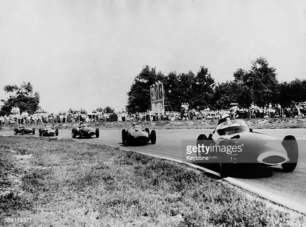 Stirling Moss of Great Britain drives the Vanwall VW 5 ahead of Jean Behra Maserati and Tony Brooks in the Vanwall during the Italian Grand Prix on 8...