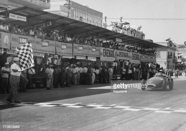Stirling Moss of Great Britain driving the Vandervell Products Vanwall VW5 takes the chequered flag to win the Pescara Grand Prix on 18 August 1957...