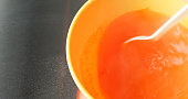 Close view of stirring orange gelatin mix into a bowl of hot water with a white plastic spoon on a stainless steel counter top.