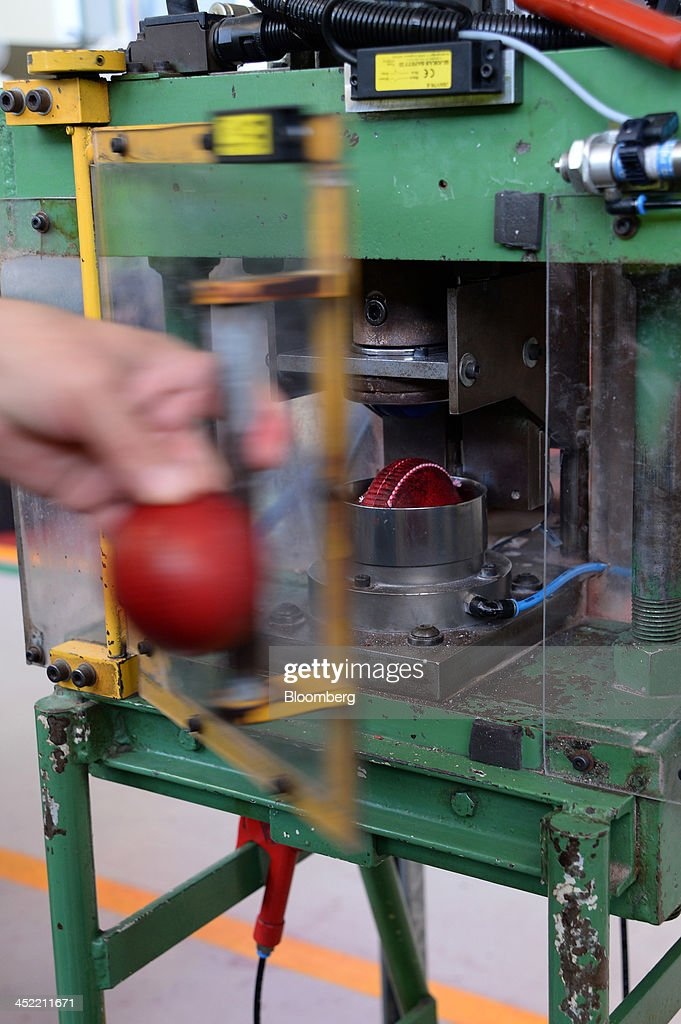 Stitched leather casings for red cricket balls are inverted in a machine before being joined at the Kookaburra Sports Pty Ltd. plant in Melbourne, Australia, on Tuesday, Nov. 26, 2013. Australian businesses need to boost efficiency to maintain growth in living standards, Reserve Bank of Australia Deputy Governor Philip Lowe said. Photographer: Carla Gottgens/Bloomberg via Getty Images
