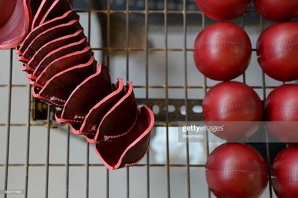 Stitched leather casings for red cricket balls, left, and ones that have been inverted sit on a rack at the Kookaburra Sports Pty Ltd. plant in Melbourne, Australia, on Tuesday, Nov. 26, 2013. Australian businesses need to boost efficiency to maintain growth in living standards, Reserve Bank of Australia Deputy Governor Philip Lowe said. Photographer: Carla Gottgens/Bloomberg via Getty Images