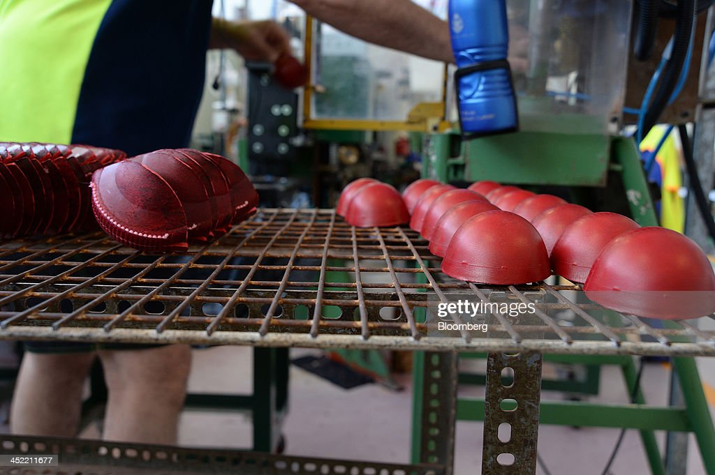 Stitched leather casings for red cricket balls, left, and ones that have been inverted sit on a rack before being joined at the Kookaburra Sports Pty Ltd. plant in Melbourne, Australia, on Tuesday, Nov. 26, 2013. Australian businesses need to boost efficiency to maintain growth in living standards, Reserve Bank of Australia Deputy Governor Philip Lowe said. Photographer: Carla Gottgens/Bloomberg via Getty Images