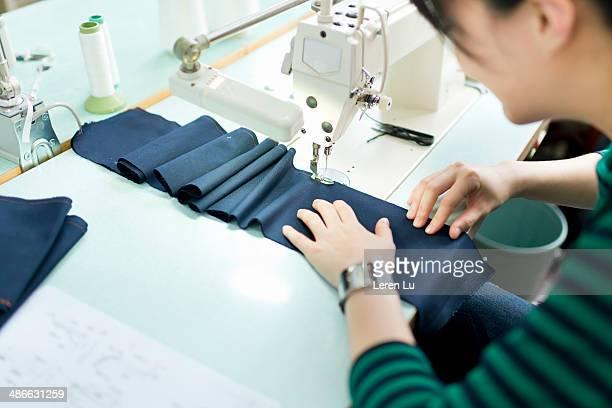 Stitching dark blue fabric with sewing machine.