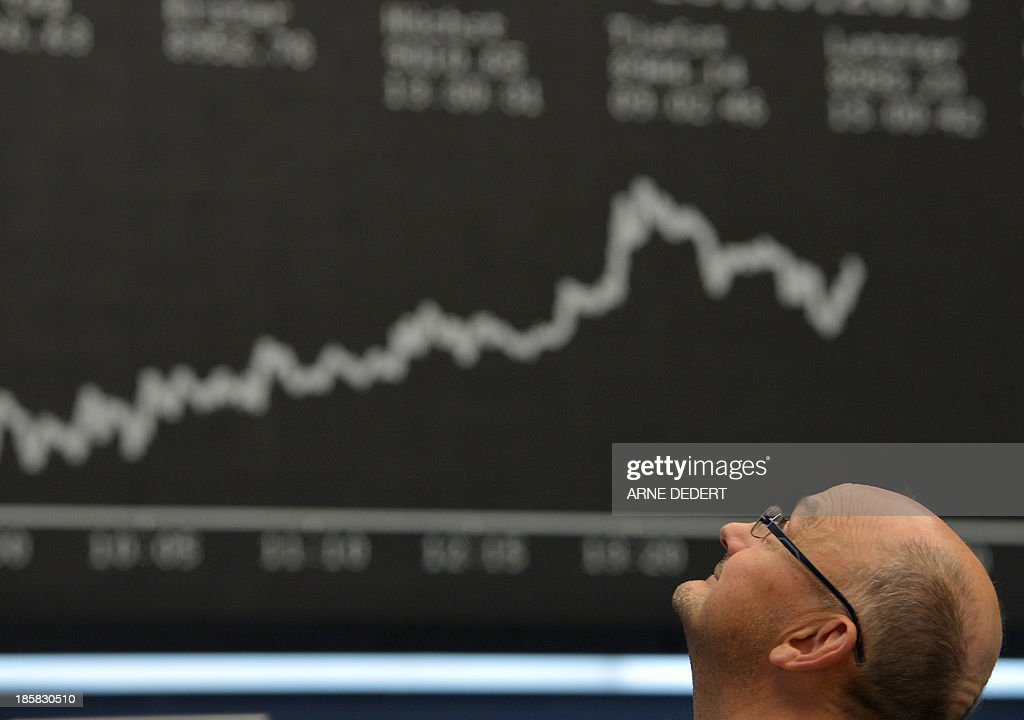 A stock broker looks up in front of the display showing the German stock market index DAX is seen at the stock exchange in Frankfurt am Main, central German on October 25, 2013. Germany's DAX stock index set a new all-time high when it briefly topped 9,000 points.