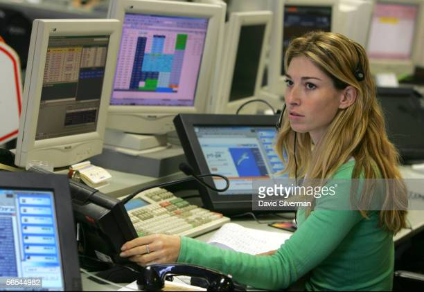 A stock broker watches a news update on Israeli Prime Minister Ariel Sharon's slightly improved state of health in the trading room of the First...