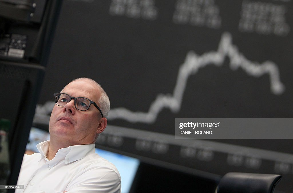 A stock broker works in front of the display showing the German stock market index DAX is seen at the stock exchange in Frankfurt am Main, central German November 7, 2013. Germany's DAX stock index set a new all-time high of 9198 after the ECB cut its key interests rates, still has other weapons up its sleeve to boost recovery in the euro, Draghi said. AFP PHOTO / DANIEL ROLAND