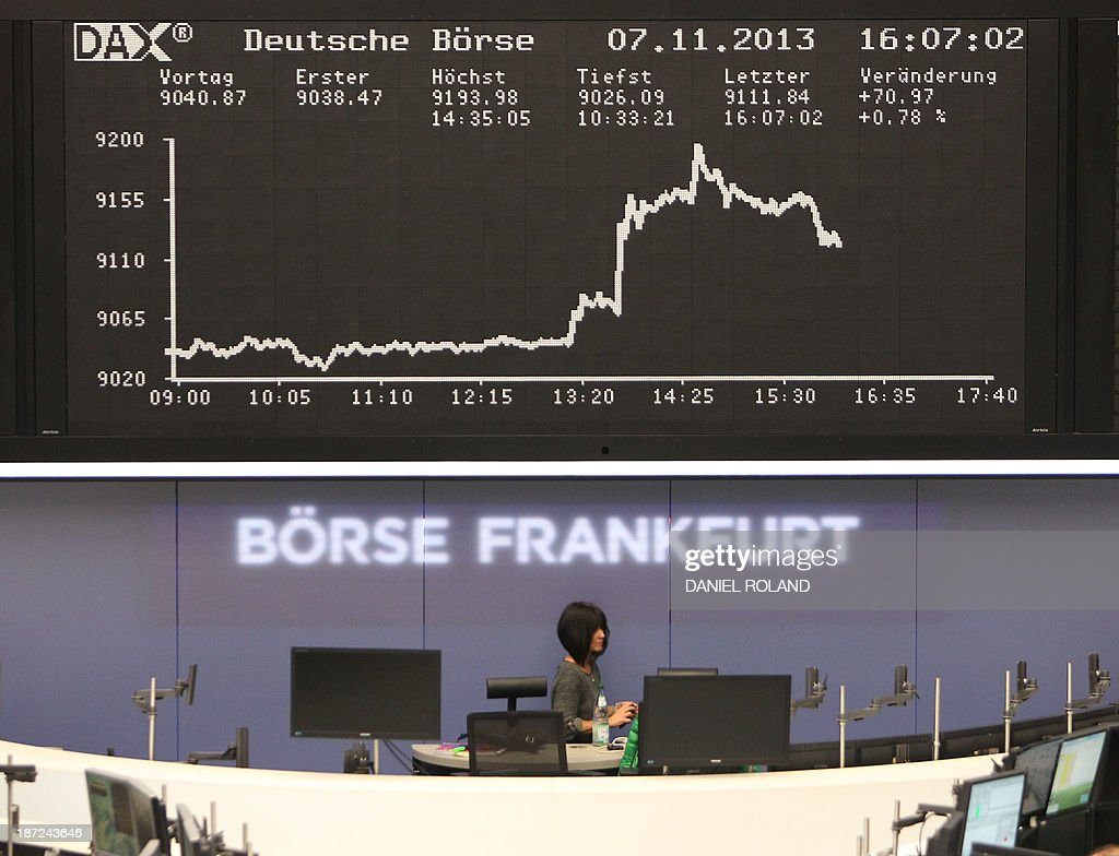 A stock broker works in front of the display showing the German stock market index DAX is seen at the stock exchange in Frankfurt am Main, central German November 7, 2013. Germany's DAX stock index set a new all-time high of 9198 after the ECB cut its key interests rates, still has other weapons up its sleeve to boost recovery in the euro, Draghi said.
