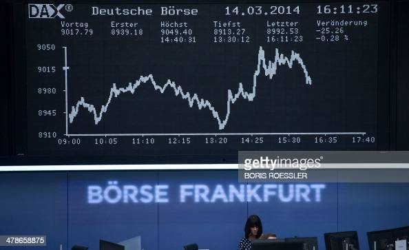 Stock brokers work in front of the display showing the German stock market index DAX at the stock exchange in Frankfurt am Main central Germany on...