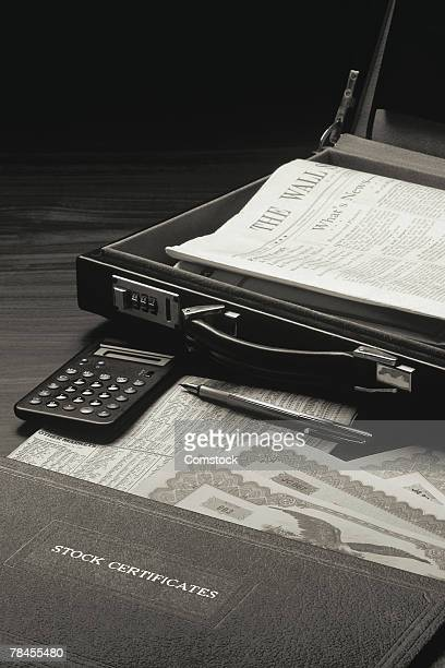 Stock certificates with calculator and briefcase