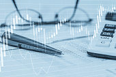 Stock data charts with spreadsheet calculator pen and glasses. Concept abstract photo of stock market financial bank accounting data analysis and monitoring.
