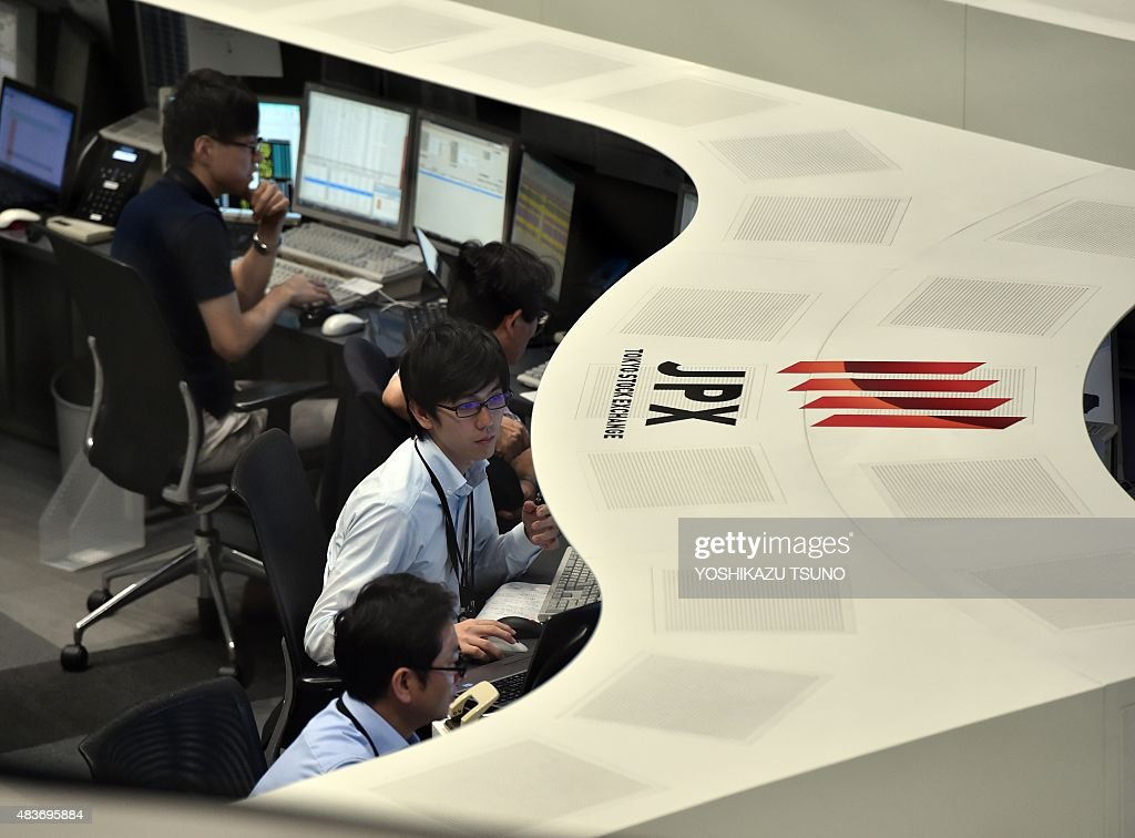 Stock exchange staffs operate at the Tokyo Stock Exchange in Tokyo on August 12 2015 Japan's share prices fell 32798 points to close at 2039277...