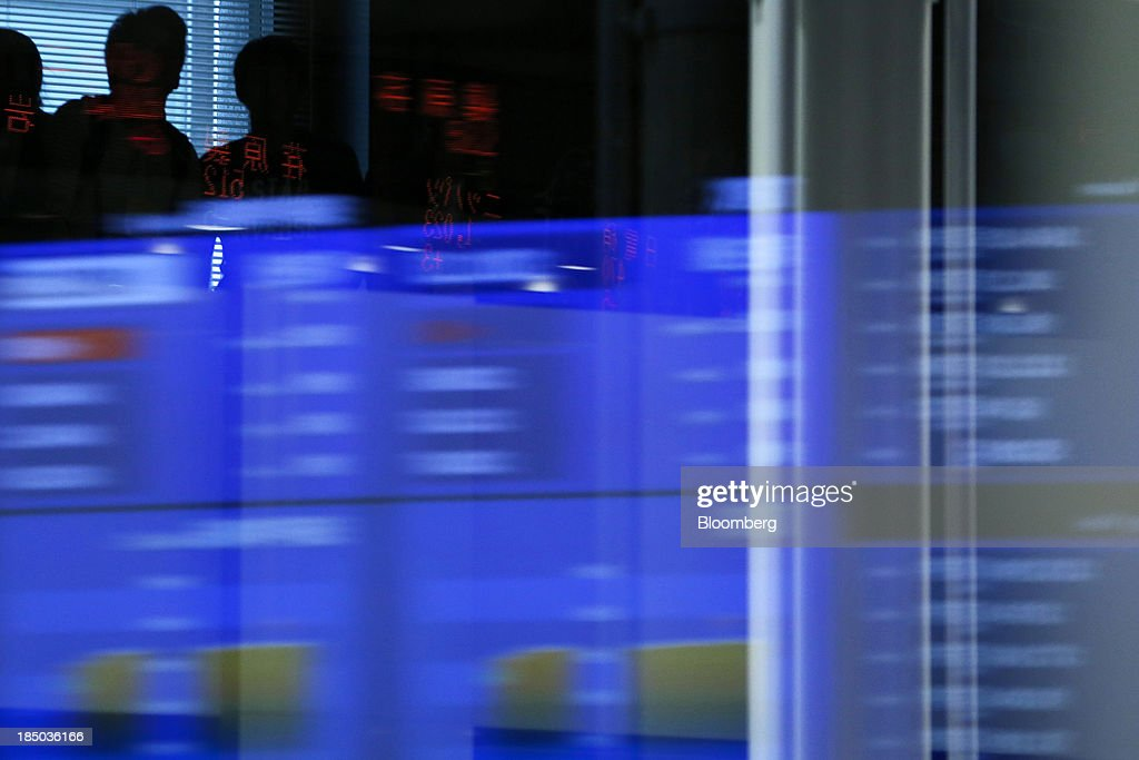 Stock figures are reflected on a glass window against the silhouettes of visitors at the Tokyo Stock Exchange (TSE) in Tokyo, Japan, on Thursday, Oct. 17, 2013. Japanese shares rose, with the Topix index climbing to a three-week high, after the U.S. Congress voted to end the government shutdown and raise the debt ceiling, ending the nation's fiscal impasse. Photographer: Kiyoshi Ota/Bloomberg via Getty Images