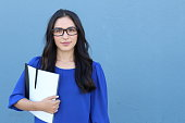 Stock image of female college student isolated on blue background.