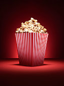 Shot of a traditional box of cinema style popcorn with spotlighting on a vibrant red background with copy space for the designer. Some of the popcorn is arranged around the base to add a different opt