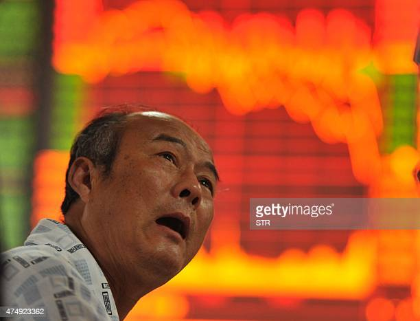 A stock investor gestures as he checks share prices at a security firm in Fuyang east China's Anhui province on May 28 2015 Chinese stocks plunged 65...