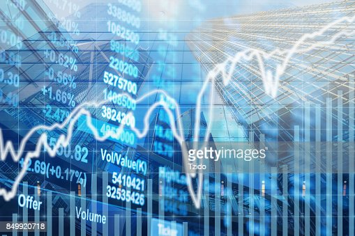 Stock market chart with information over the Modern business building glass of skyscrapers, business economy trading and finance concept : Stock Photo