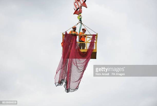 Stock photo of construction workers in a cradle fitting safety netting at the construction site of the new offices of Bloomberg situated between...