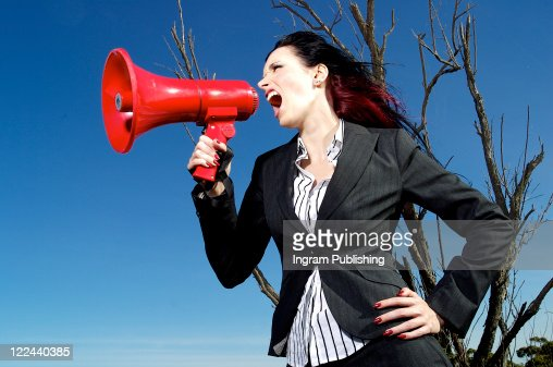 A stock photograph of a beautiful woman yelling into a mega phone. : Stock Photo