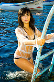 A stock photograph of a beautiful young woman posing on a ladder by the water in Malta.
