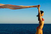 A stock photograph of a free young woman holding her sarong into the breeze,