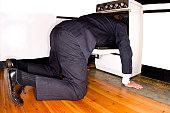A stock photograph of a man committingásuicide by sticking his head in an oven.