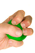 A stock photograph of a man's hand squeezing a green stress ball.
