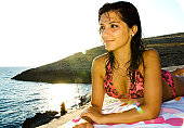A stock photograph of an attractive young model relaxing on her towel by the sea in Malta.