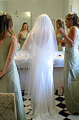 A stock photograph of brides maids prepare a bride for her wedding.