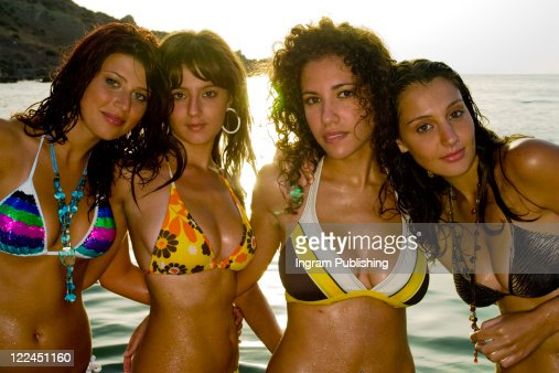 A Stock Photograph Of Four Gorgeous Young Girls Relaxing By The Ocean During A Hot Summers