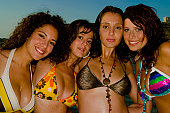 A stock photograph of four gorgeous young girls relaxing by the ocean during a hot summers day in Malta in their bikinis.