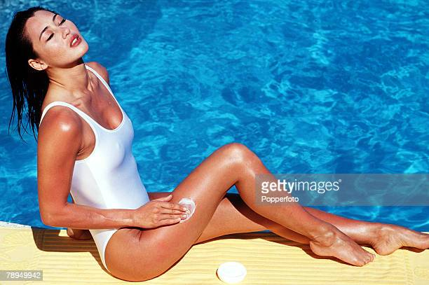 Stock Photography A fulllength view of a young woman with eyes closed wearing a white swimming costume and lying in the sun by a swimming pool whilst...