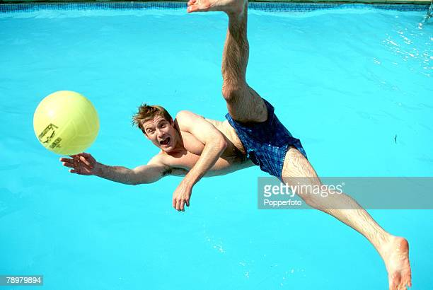 Stock Photography A portrait of a young man leaping midair for a ball with legs stretched while he falls into a swimming pool