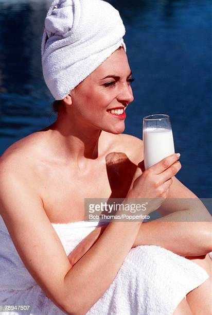 Stock Photography Profile portrait of a young woman with towels around both hair and body sitting near some water drinking a glass of milk in the...
