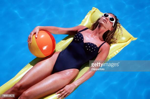 Tanned woman wearing swimming costume and sunglasses floating on a lilo in a pool and clutching a beach ball Overhead view looking down