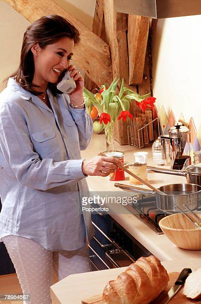 Young pregnant woman standing in the kitchen talking on the telephone while stirring the contents of a saucepan on the cooker