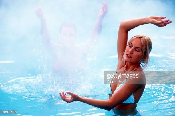 Stock Photography Young woman and a man standing in an steamy pool of blue water while making carefull geometric movements with their arms Cross...