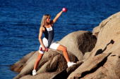 Young woman wearing black white lycra fitness gear stretches her legs between two rocks by the sea while lifting hand weights in an aerobic excercise