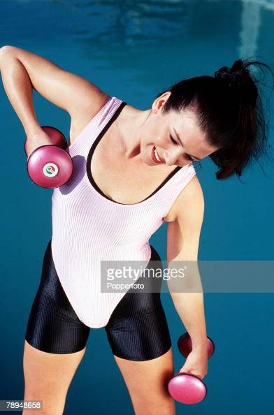 Stock Photography Young woman wearing lycra fitness gear exercises in front of a swimming pool with two hand weights High angle view looking down