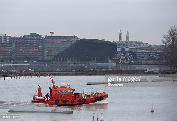 A stock pile of coal sits near the Salmasaari Power Station as a pilot boat sails in the harbour in Helsinki Finland on Monday March 9 2015 Finland...