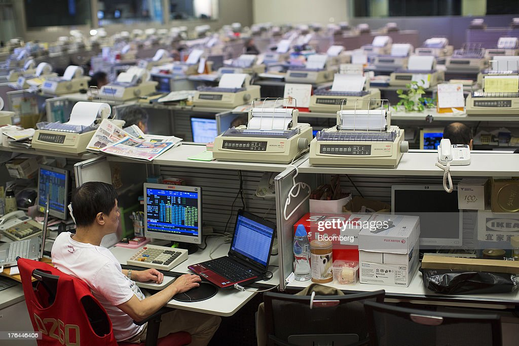 A stock trader looks at a laptop computer at his desk on the trading floor of the Hong Kong Stock Exchange in Hong Kong, China, on Tuesday, Aug. 13, 2013. Hong Kong Exchanges & Clearing Ltd., operator of the Hong Kong Stock Exchange, is scheduled to release second-quarter results tomorrow. Photographer: Jerome Favre/Bloomberg via Getty Images