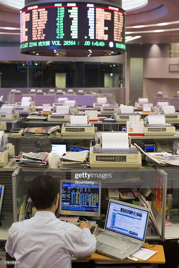 A stock trader sits at his desk facing an electronic board on the trading floor of the Hong Kong Stock Exchange in Hong Kong, China, on Tuesday, Aug. 13, 2013. Hong Kong Exchanges & Clearing Ltd., operator of the Hong Kong Stock Exchange, is scheduled to release second-quarter results tomorrow. Photographer: Jerome Favre/Bloomberg via Getty Images