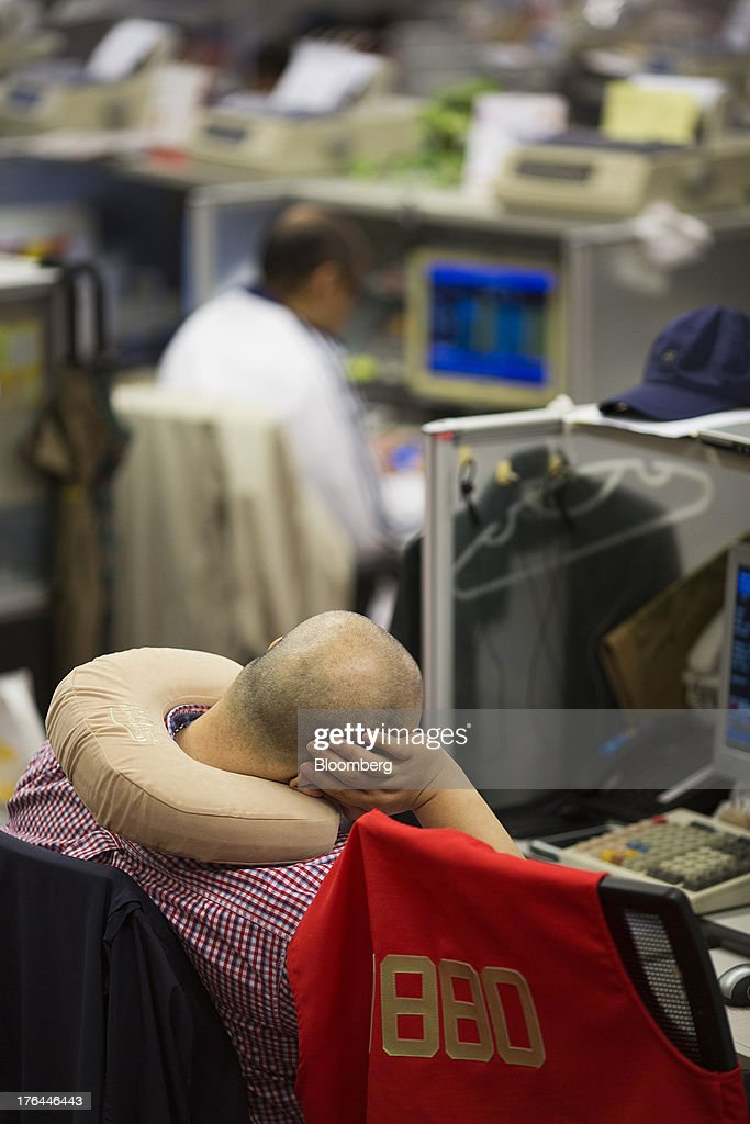 A stock trader wearing a neck pillow sits at his desk on the trading floor of the Hong Kong Stock Exchange in Hong Kong, China, on Tuesday, Aug. 13, 2013. Hong Kong Exchanges & Clearing Ltd., operator of the Hong Kong Stock Exchange, is scheduled to release second-quarter results tomorrow. Photographer: Jerome Favre/Bloomberg via Getty Images