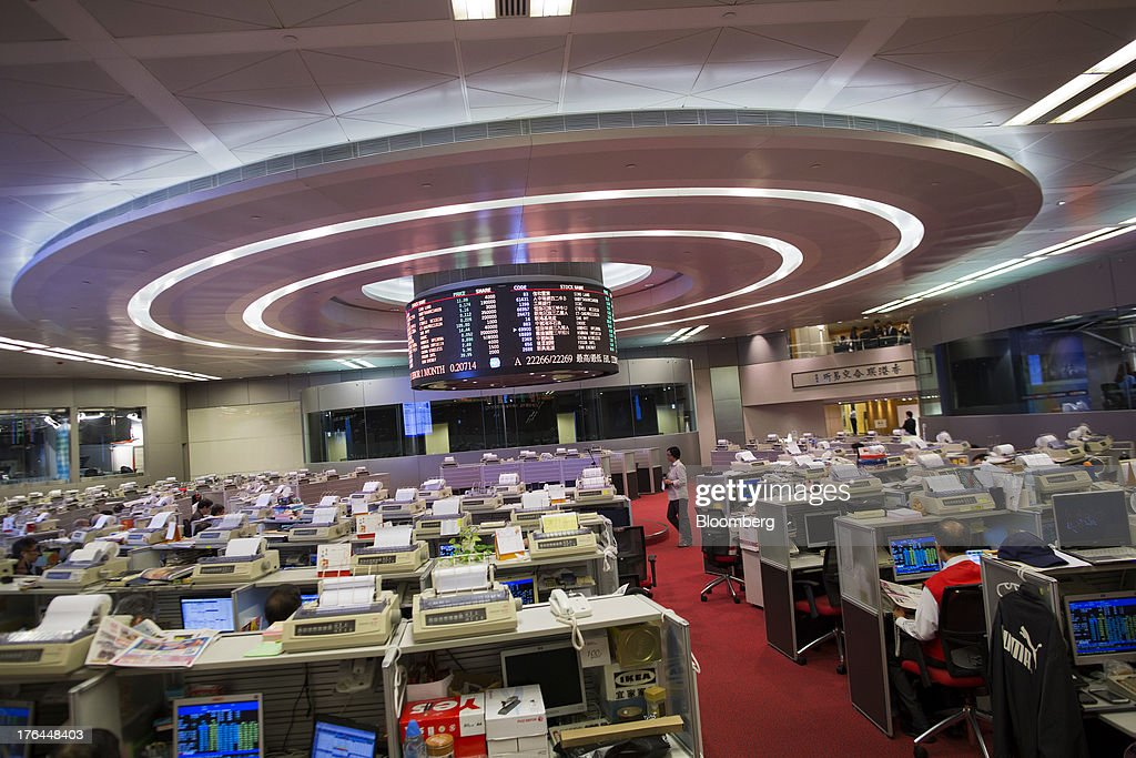 Stock traders' desks sit around an electronic board on the trading floor of the Hong Kong Stock Exchange in Hong Kong, China, on Tuesday, Aug. 13, 2013. Hong Kong Exchanges & Clearing Ltd., operator of the Hong Kong Stock Exchange, is scheduled to release second-quarter results tomorrow. Photographer: Jerome Favre/Bloomberg via Getty Images